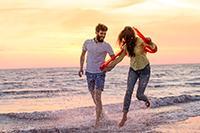 Paar springt über Wellen